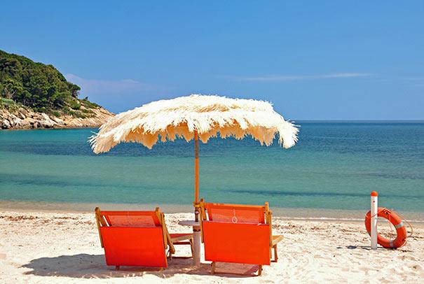 Strandliegen und Sonnenschirm am Strand der Fetovaia-Bucht