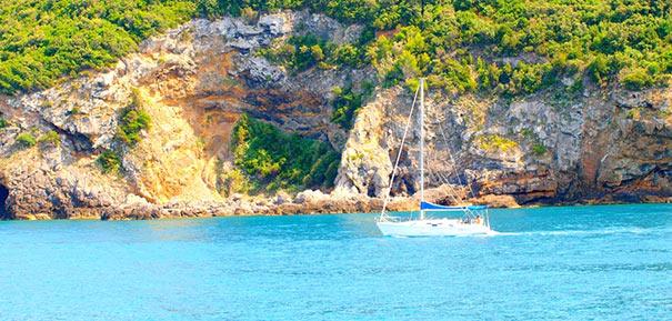Küste der Insel Giglio mit kleinem Segelschiff
